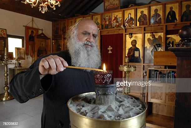 Father Savvas Michaelides lights a candel inside his humble church near the coastal town of Limassol 15 November 2007 Standing outside his humble...