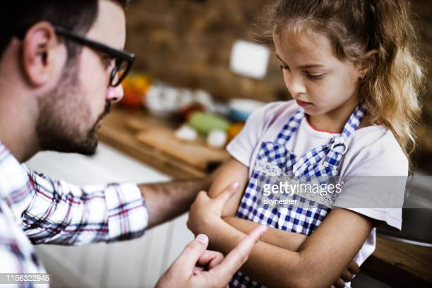 father scolding his daughter at home. - censura imagens e fotografias de stock