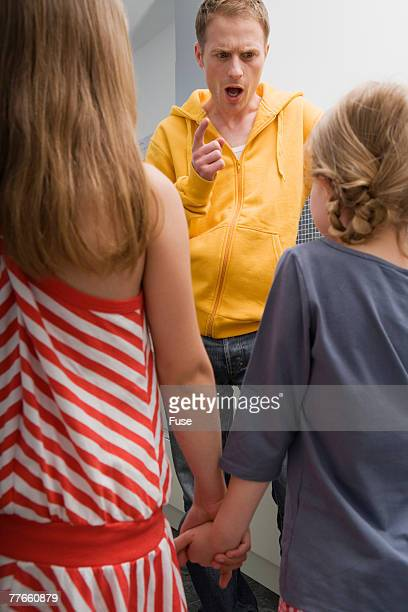 Father Scolding Two Girls