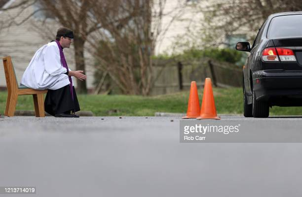 Father Scott Holmer of St Edward the Confessor Catholic Church holds confession in the church parking lot on March 20 2020 in Bowie Maryland Holmer...