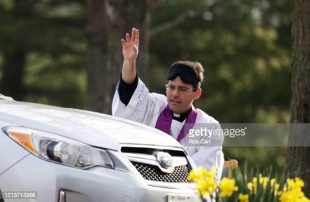 Father Scott Holmer of St Edward the Confessor Catholic Church makes the sign of the cross after holding confession in the church parking lot on...