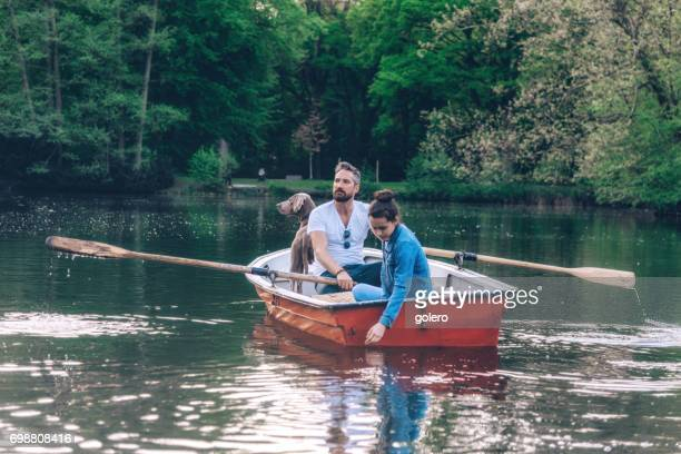 father sculling row boat with teenage daughter and Weimaraner dog