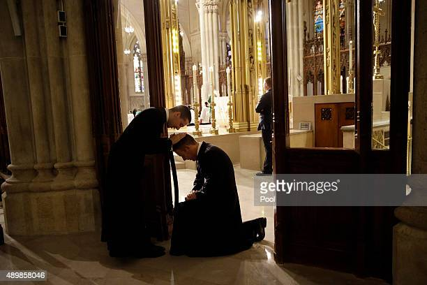 Father Sean Connolly left a newly ordained priest gives a first priestly blessing while waiting the arrival of Pope Francis September 24 2015 in New...
