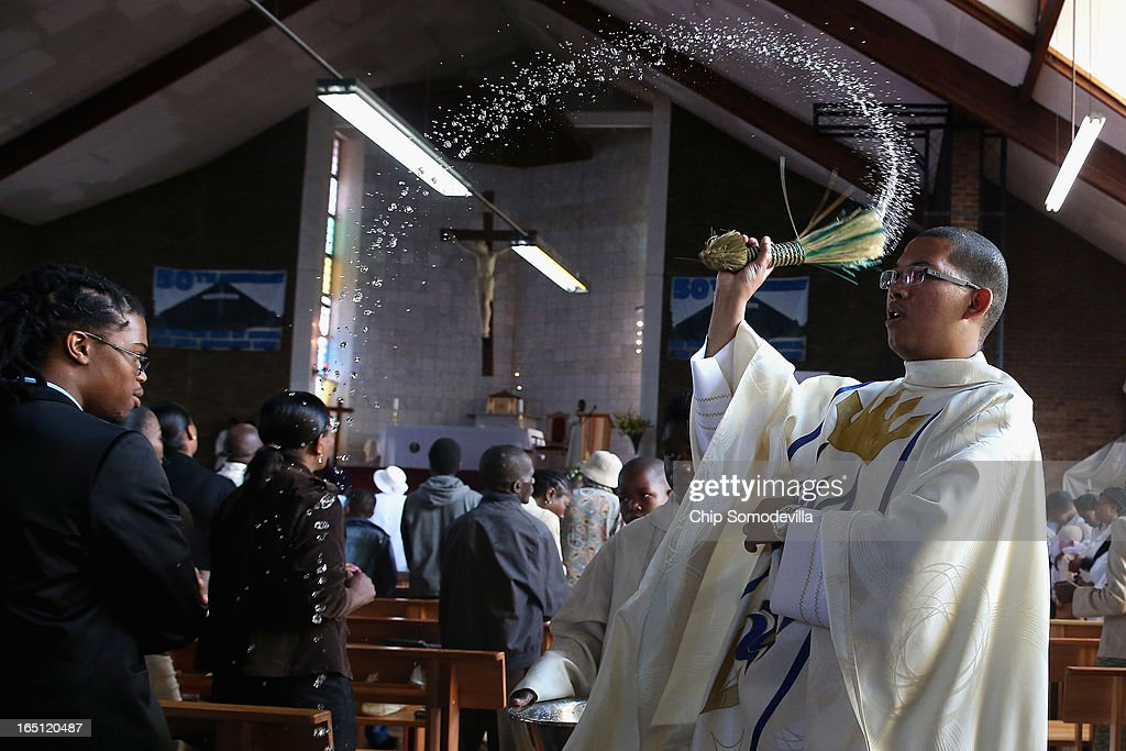 Father Sebastian Rossouw O.M.I. sprinkes holy water on congregants during Easter services at Regina Mundi Catholic Church in the Soweto area March 31, 2013 in Johannesburg, South Africa. A central gathering place during he anti-apartheid struggle, the church held prayers for former South African President Nelson Mandela, 94, who is in the hospital for the third time since December with lung problems. Referring to Mandela by clan name, Madiba, President Jacob Zuma said, 'We appeal to the people of South Africa and the world to pray for our beloved Madiba and his family and to keep them in their thoughts.' Mandela's lungs were damaged when he contracted tuberculosis during his 27 years in the infamous Robben Island prison. Mandela became the nation's first democratically elected president in 1994 following the end of apartheid.