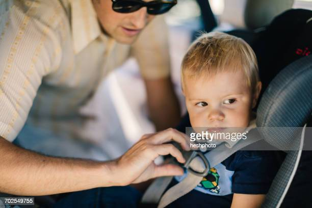 father securing young son in car seat - heshphoto stock pictures, royalty-free photos & images