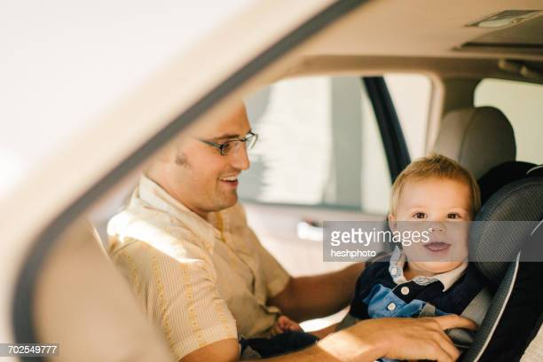 father securing young son in car seat - heshphoto stockfoto's en -beelden