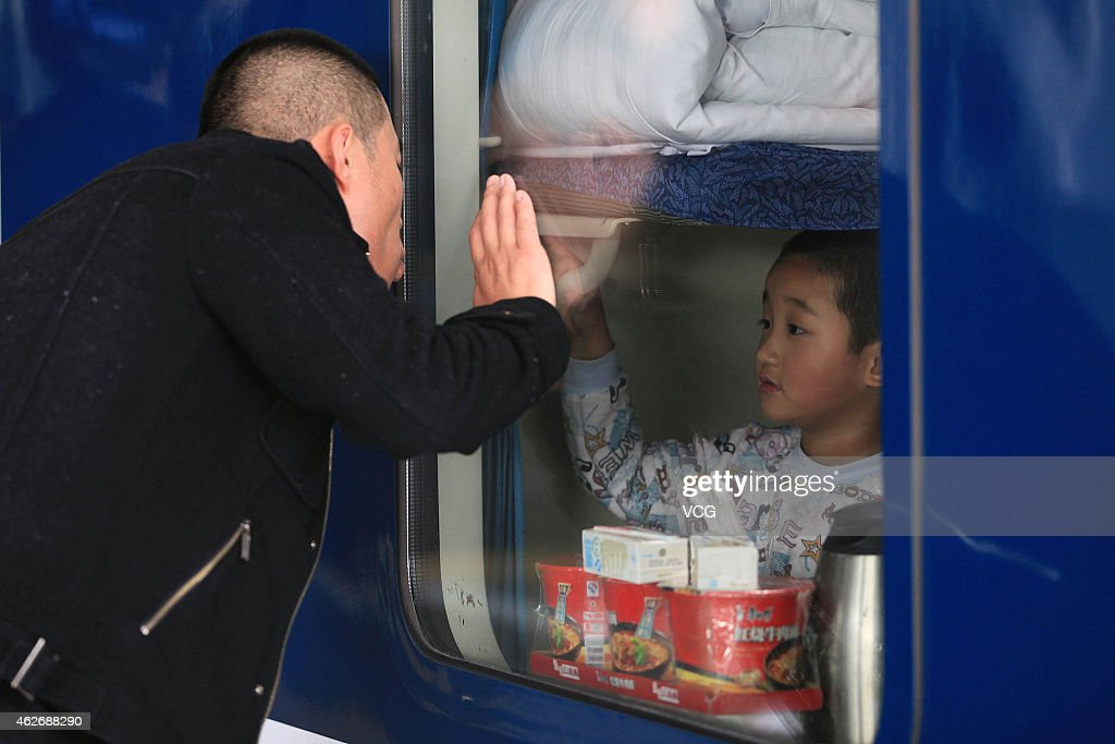 A father sees his son off before the train setting off in the afternoon at Shenzhen Railway Station on January 28, 2015 in Shenzhen, Guangdong province of China. With the approaching Spring Festival, more and more migrant workers returned their hometowns to gather with their family. However, the various touching farewell scenes shocked us more.