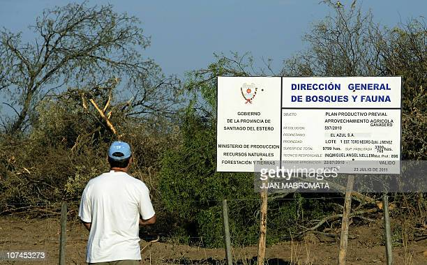 Father Sergio looks at a sign by Santiago del Estero government allowing to clear native forests in preparation for agriculture in Pozo Hondo...