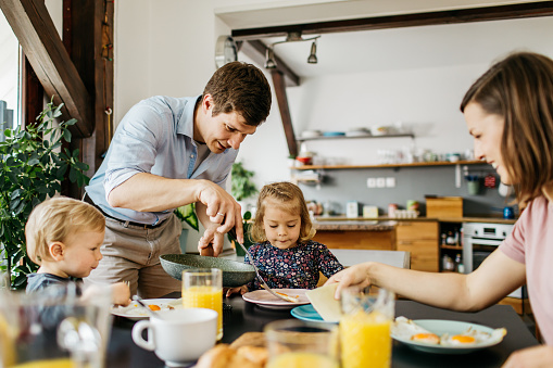 Father serving breakfast to family 1146028609