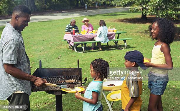 Father serving children (5-13) grilled burgers at picnic