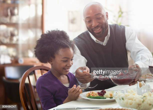 father serving daughter at holiday table - cranberry sauce stock photos and pictures