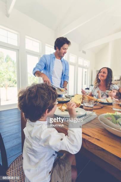 father serving food to his family. - vertical imagens e fotografias de stock