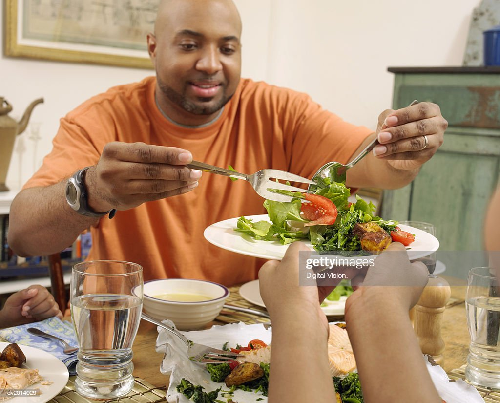 Father Serving Salad on a Plate : Stock Photo