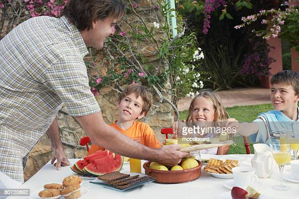 Father serving slices of pineapple to children (6-11) sitting at outdoor table