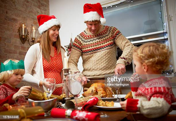 father serving up christmas dinner to family. - evening meal stock pictures, royalty-free photos & images