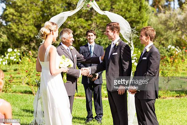 father shaking hands with groom during wedding ceremony - religious occupation stock pictures, royalty-free photos & images