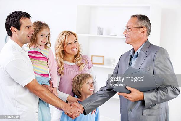 Father shaking hands with Insurance Agent.