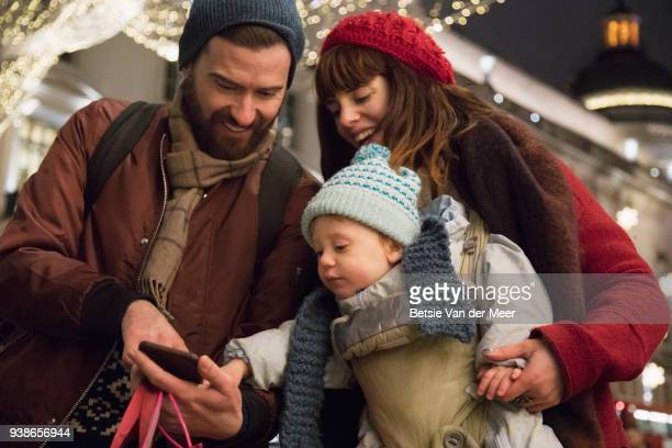father shares selfies taken with wife and child in christmas shopping street.