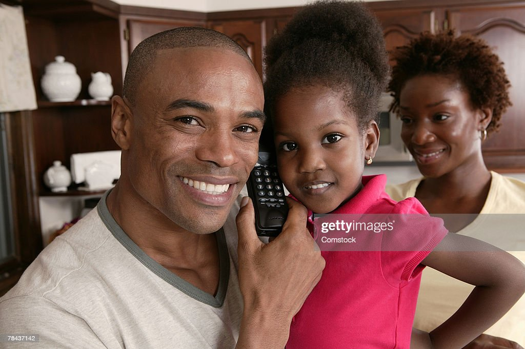 Father sharing telephone with daughter : Stockfoto