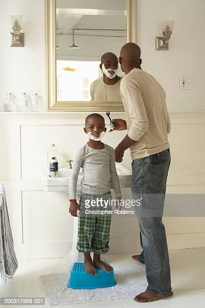 Father shaving by son (5-7) wearing shaving foam, portrait of boy