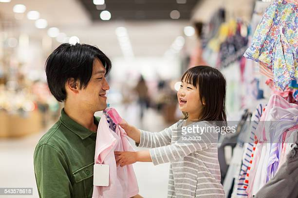 Father shopping for a dress with his young daughter