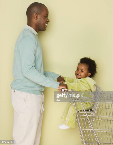Father shopping with baby daughter in shopping cart