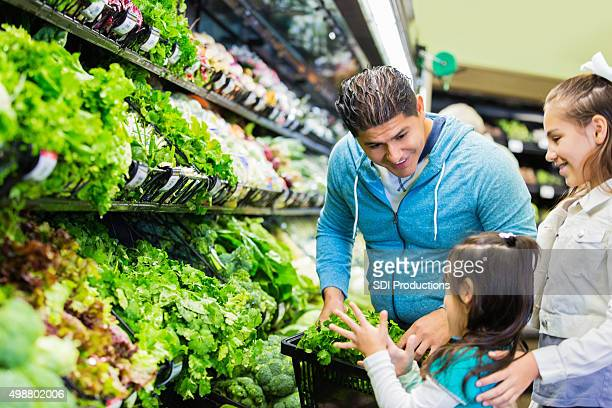 Father shopping with daughters for groceries in local supermarket