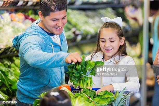 Father shopping with elementary age daughter in grocery store