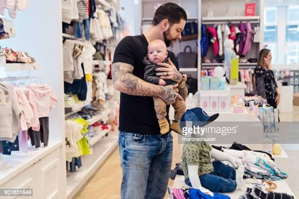 父は子供の店で若い赤ちゃんと買い物。