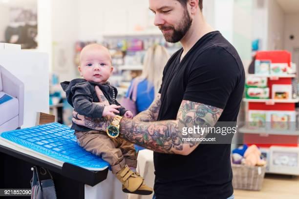 """pai de compras com baby jovens numa loja de crianças. - """"martine doucet"""" or martinedoucet - fotografias e filmes do acervo"""
