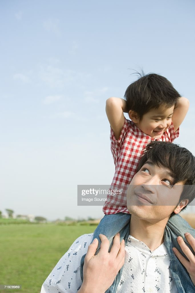 Father shoulder carrying his son : Stock Photo