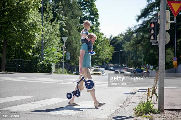 Father shoulder carrying toddler son over pedestrian crossing
