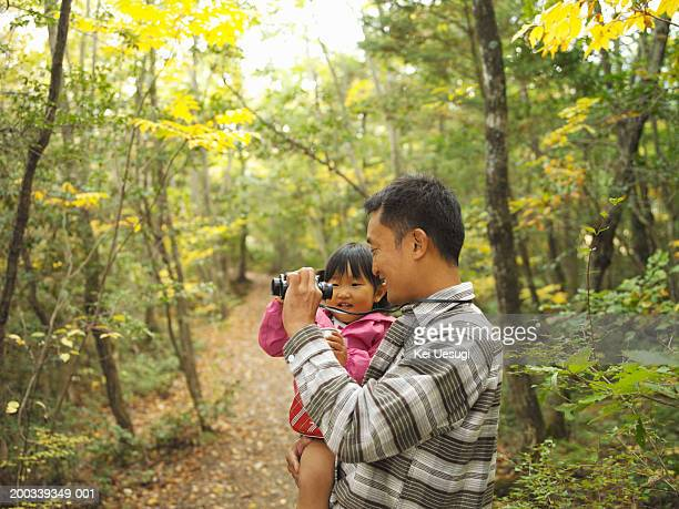 Father showing binoculars to daughter (2-4) in forest