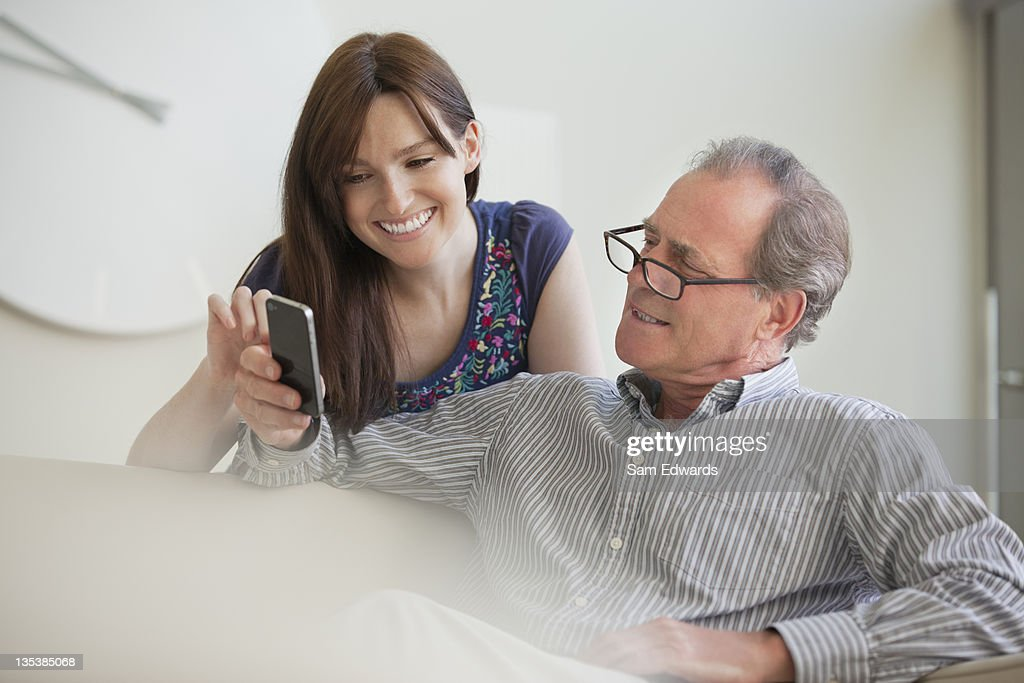Father showing cell phone to daughter : Stock Photo