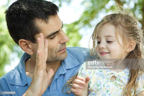 Father showing daughter his hand
