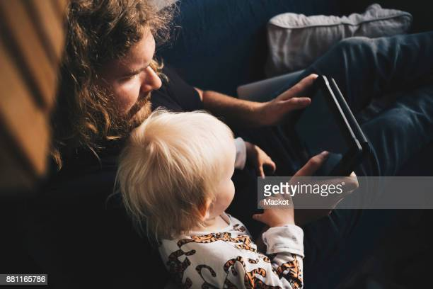 Father showing digital tablet to girl while sitting on sofa at home