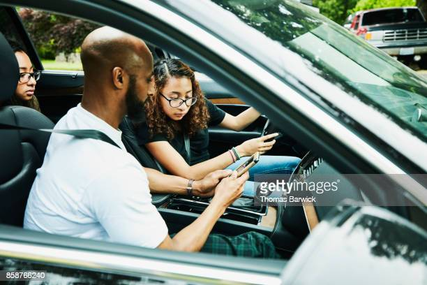 Father showing directions on smartphone to daughter while teaching her to drive