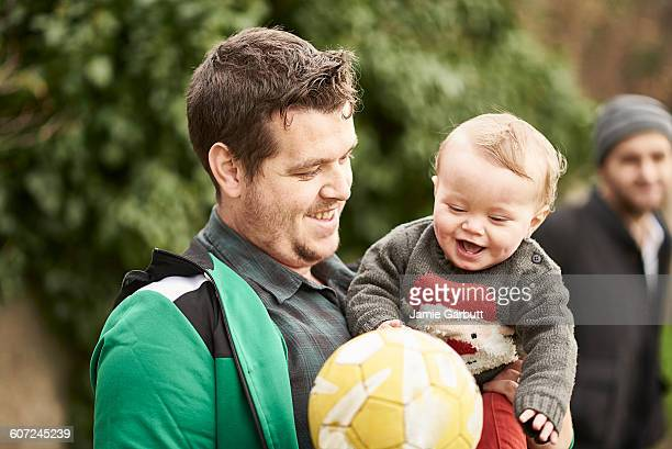 A father showing his baby son a football