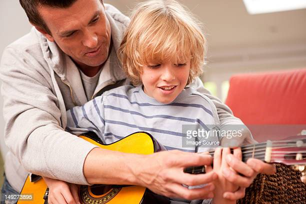 Father showing his son how to play a guitar