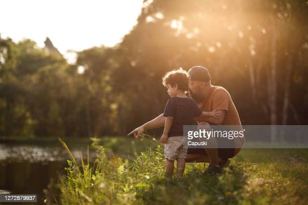 father showing lake to his son - simple living stock pictures, royalty-free photos & images