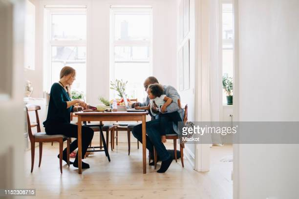 father showing laptop to daughter while mother cutting vegetables at table in house - tavolo da soggiorno foto e immagini stock