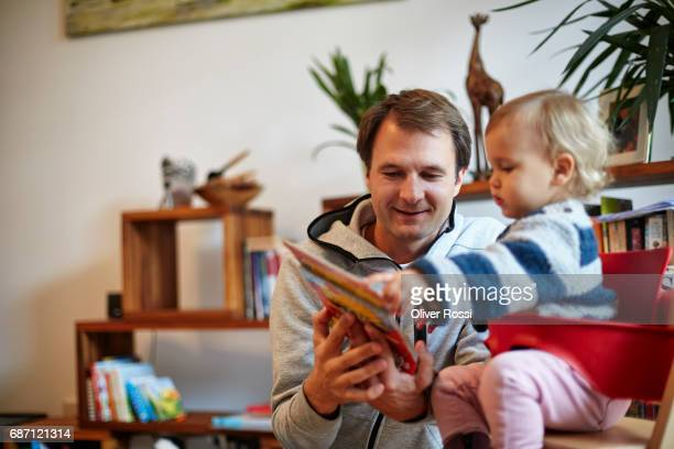 father showing picture book to little daughter - leanincollection stock pictures, royalty-free photos & images