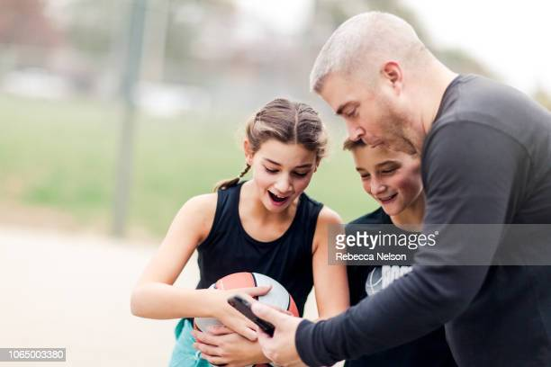 father showing pre-teen boy and girl video of their basketball game on his smartphone