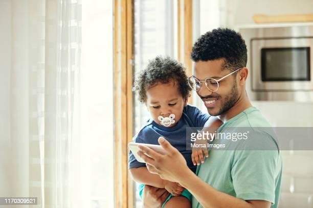 vader toont smart phone aan zoon door venster - afro amerikaanse etniciteit stockfoto's en -beelden