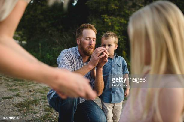 Father showing son how to whistle with grass