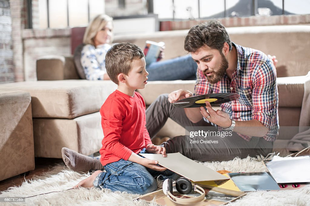 Father showing vinyl record to son at home : Stock Photo