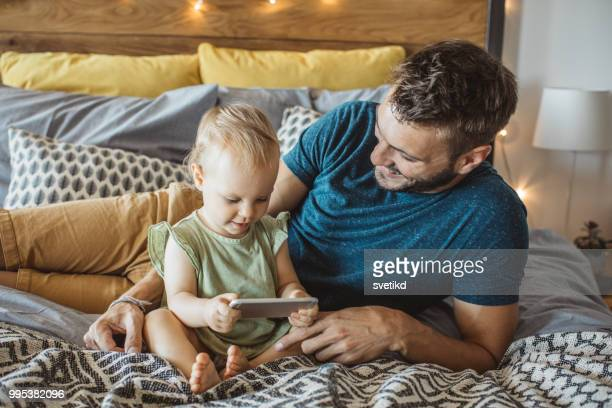 Father shows little daughter something on phone