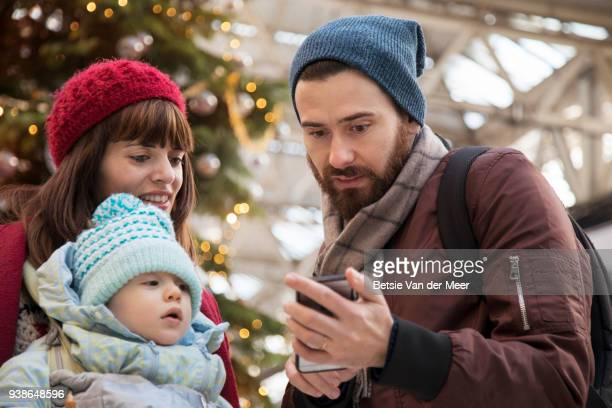 Father shows mobile phone to mother and child in departure hall.