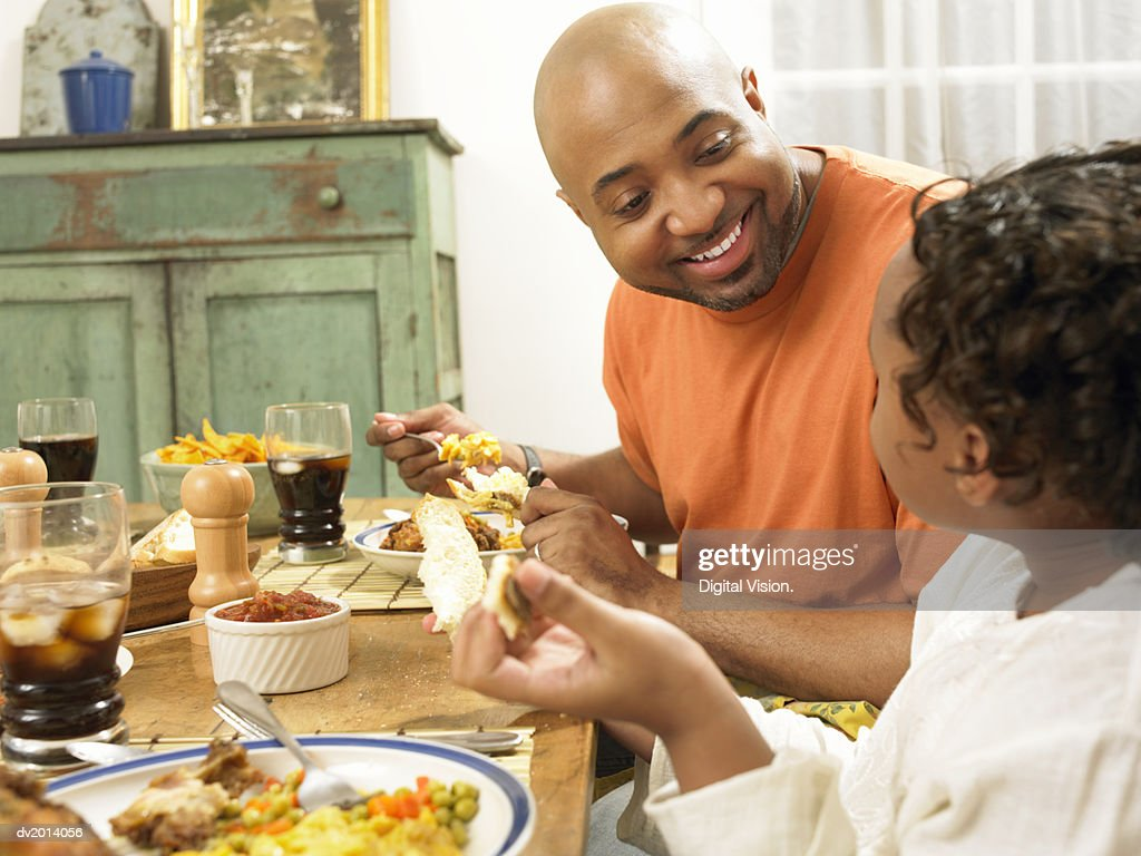 Father Sits at the Kitchen Table With His Young Daughter Talking and Eating Dinner : Stock Photo