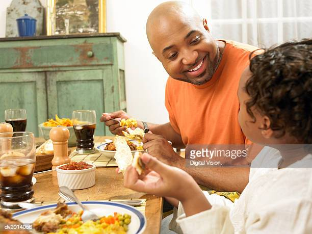 Father Sits at the Kitchen Table With His Young Daughter Talking and Eating Dinner